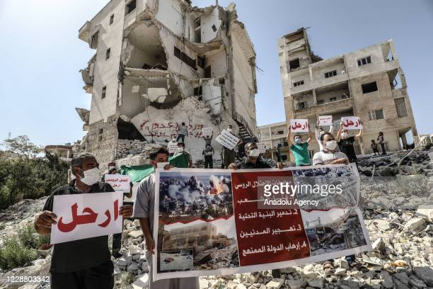 People hold banners near damaged and partly collapsed buildings during a protest against Russia on the 6th year of Russian involvement in the Syrian...