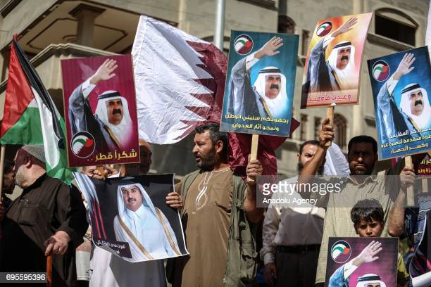 People hold banners of Emir of Qatar Tamim bin Hamad Al Thani and his father Former Emir of Qatar Hamad bin Khalifa Al Thani during a demonstration...