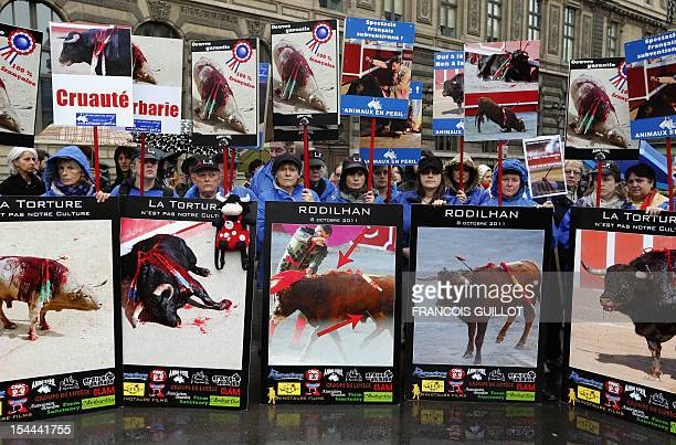 People hold banners reading ''Torture is not in our culture'' ''cruelty'' during a demonstration against bullfighting on October 20 2012 in Paris...