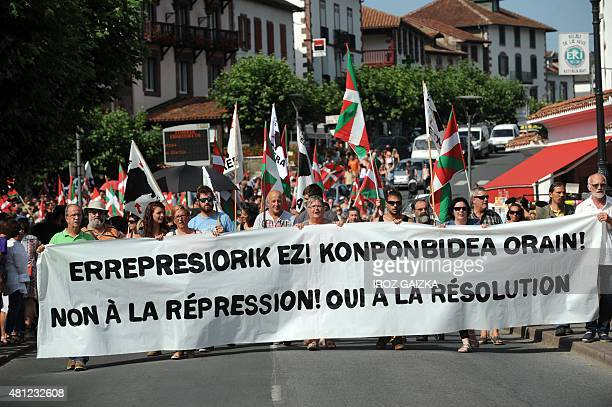 People hold Basque flags and a banner reading 'No to repression Yes to resolution' on July 18 2015 in SaintJeanPieddePort southwestern France during...