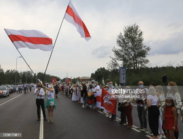 People hold Belarussian opposition flags as people form a human chain from Vilnius to Medininkai along the border with Belarus to show solidarity...