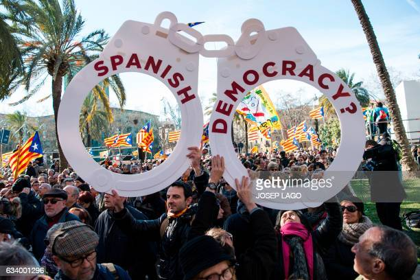 TOPSHOT People hold big handcuffs reading Spanish democracy outside the TSJC in Barcelona on February 6 2017 during the first day of the trial of...