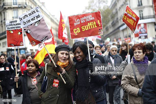 People hold boards which ask to raise wages and pensions and denouncing gifs for the rich during a demonstration of workers against a government...