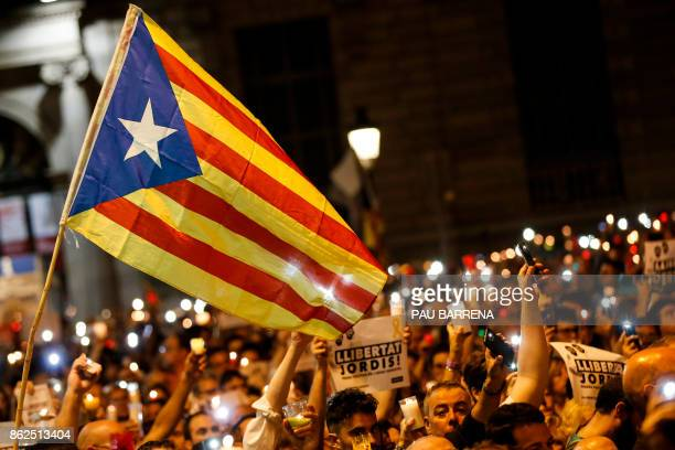 TOPSHOT People hold candles and a Catalan proindependence 'Estelada' flag during a demonstration in Barcelona against the arrest of two Catalan...
