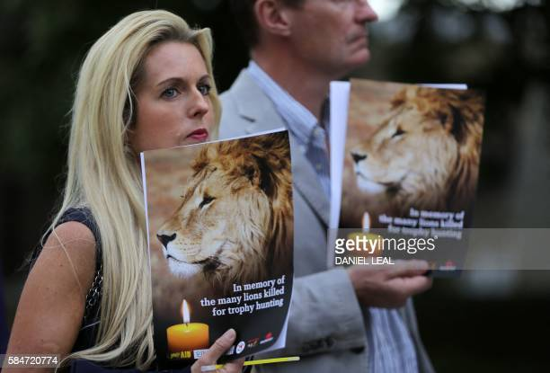 People hold candles and pamphlets shows an image of Cecil the lion at a vigil in central London on July 30 2016 Cecil was killed by American dentist...