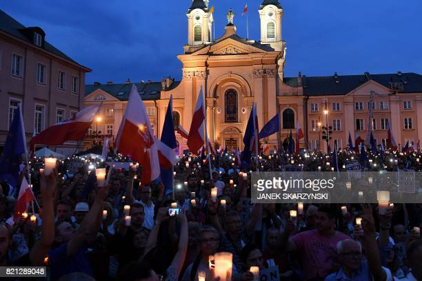 People hold candles and Polish national flags as they take part in demonstration in front of the Polish Supreme Court on July 23 2017 in Warsaw to...