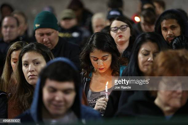 People hold candles as they attend a vigil at the San Manuel Stadium to remember those injured and killed during the shooting at the Inland Regional...