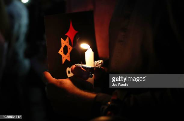 People hold candles as they gather together for a CommunityWide Solidarity Vigil at the Holocaust Memorial Miami Beach to remember the victims of the...