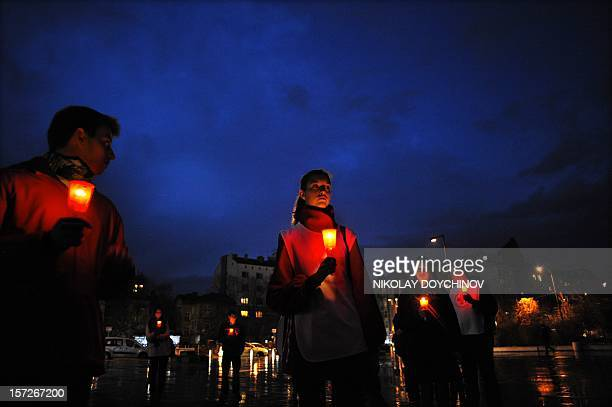 People hold candles as they mark the World AIDS Day in Sofia on December 1 2012 AFP PHOTO / NIKOLAY DOYCHINOV