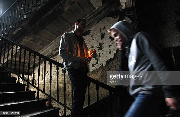 People hold candles as they mourn inside the burned trade union building in the southern Ukrainian city of Odessa on May 4 2014 Flowers candles and...