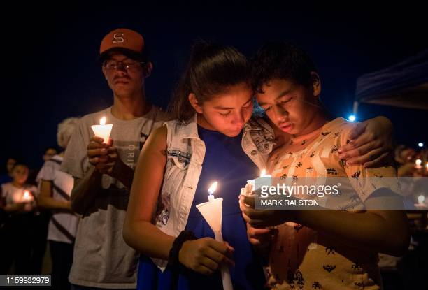 TOPSHOT People hold candles as they pray during a candlelight vigil at the Immanuel Church for victims of a shooting that left a total of 22 people...