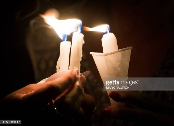 People hold candles as they pray during a candlelight vigil at the Immanuel Church for victims of a shooting that left a total of 22 people dead at...