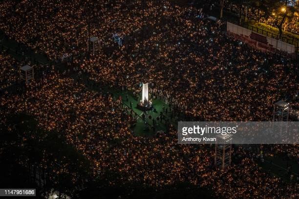 People hold candles as they take part in a candlelight vigil at Victoria Park on June 4, 2019 in Hong Kong, China. As many as 180,000 people were...
