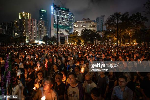 People hold candles as they take part in a candlelight vigil at Victoria Park on June 4, 2019 in Hong Kong, China. As many as 180,000 people are...