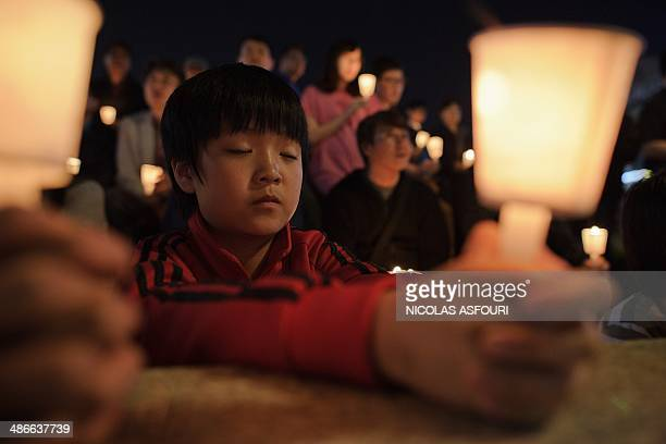 People hold candles at a vigil for students among the missing passengers of a South Korean capsized ferry in central Ansan on April 25 2014 The...