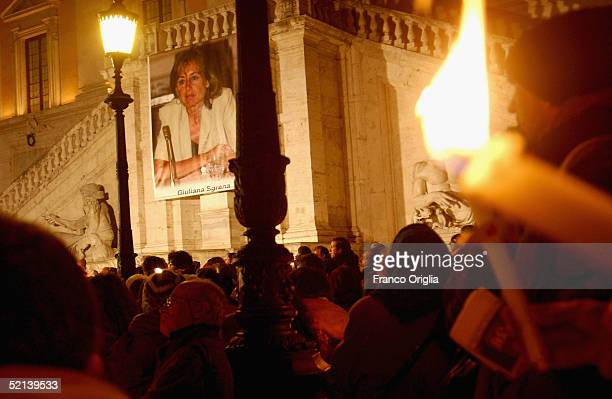 People hold candles during a meeting of solidarity for kidnapped journalist Giuliana Sgrena in the Capitole Square on February 5 in Rome, Italy....