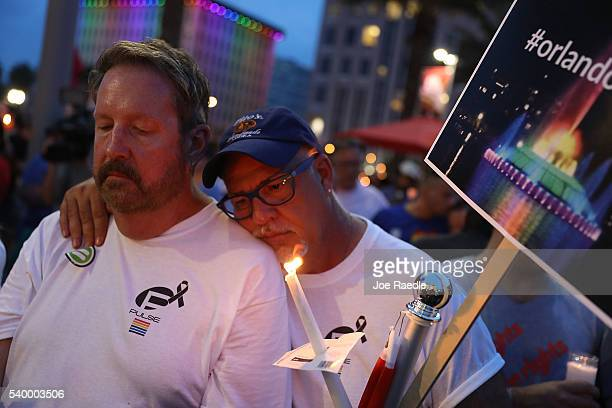 People hold candles during a memorial service at the Dr Phillips Center for the Performing Arts for the victims of the Pulse gay nightclub shooting...