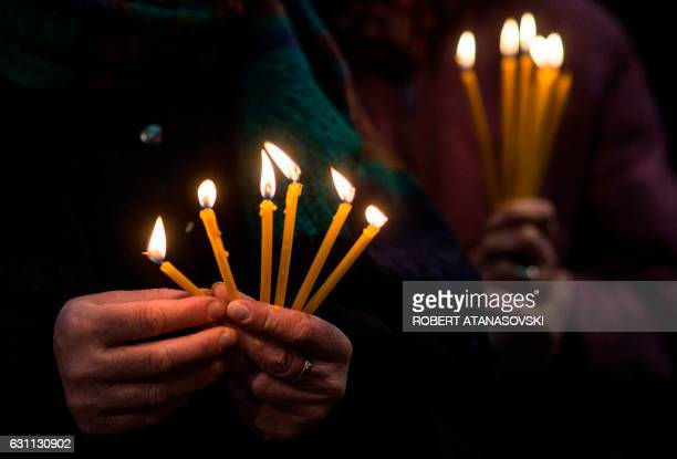 People hold candles during a religious service at St Clement Cathedral to celebrate the Orthodox Christmas in Skopje on January 7 2017 Eastern...