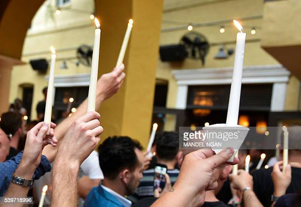 People hold candles during a vigil for the victims of the Pulse club shooting at the Ember restaurant and bar in Orlando Florida on June 12 2016 49...