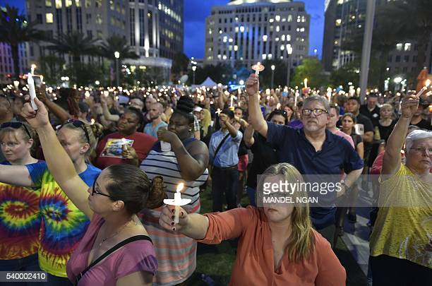 People hold candles during a vigil for the victims of the Pulse nightclub shooting on June 13 2016 at the Dr Phillips Center for the Performing Arts...