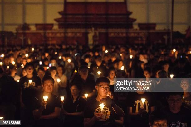 TOPSHOT People hold candles during a vigil in Hong Kong on June 4 to mark the 29th anniversary of the 1989 Tiananmen crackdown in Beijing Crowds...