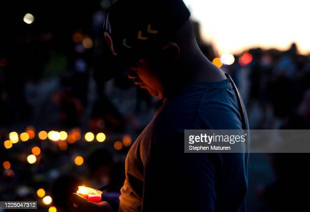 People hold candles during a vigil in honor of Philando Castile, at the site where he was killed, on July 6, 2020 in Falcon Heights, Minnesota....