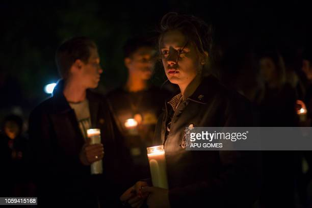 People hold candles during a vigil to pay tribute to the victims of a shooting in Thousand Oaks, California, on November 8, 2018. - A 28-year-old US...