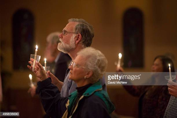 People hold candles during a worship and prayer vigil service for victims on the day after the mass shootings at the Inland Regional Center, December...