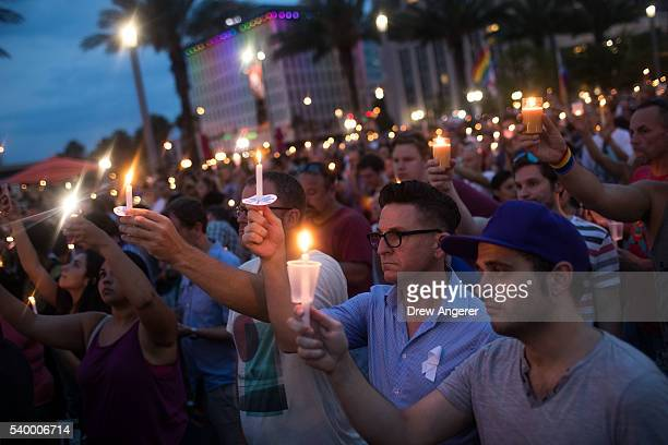 People hold candles during an evening memorial service for the victims of the Pulse Nightclub shootings at the Dr Phillips Center for the Performing...