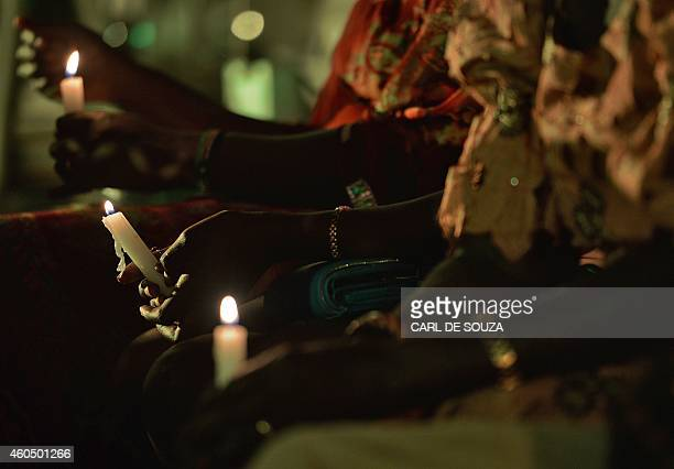 People hold candles during an evening of remembrance to mark one year since the start of the recent conflict in South Sudan organised by Amnesty...