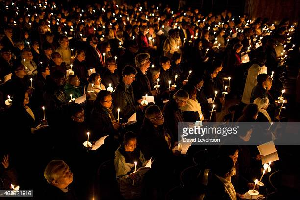 People hold candles during The Easter Vigil service on the evening of Holy Saturday at Westminster Cathedral on April 4 2015 in London England Easter...