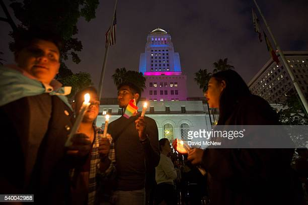 People hold candles near City Hall which is lit in the colors of the rainbow flag to honor the LGBT victims of the worst mass shooing in United...