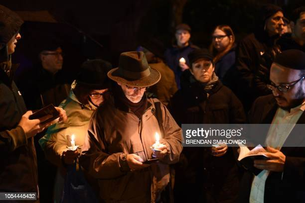 People hold candles outside the Tree of Life Synagogue after a shooting there left 11 people dead in the Squirrel Hill neighborhood of Pittsburgh on...