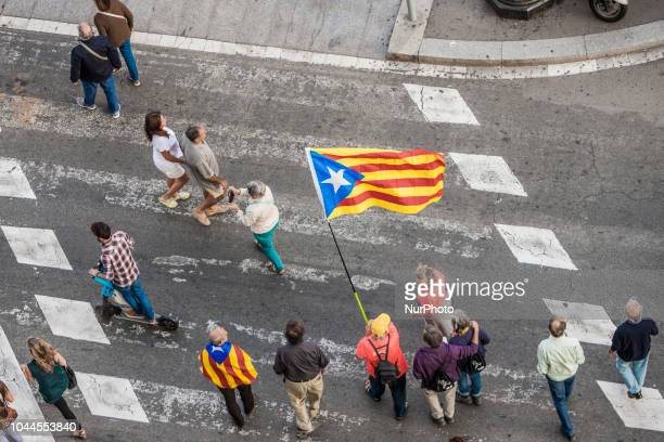 People hold catalan flags during the demonstration in Barcelona for the one year anniversary of catalan elections for independence on 1st of october...