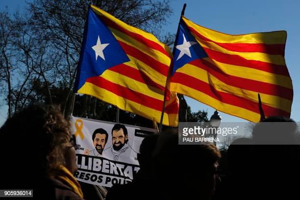 People hold Catalan proindependence 'Estelada' flags and a flag depecting images of Catalan separatist leaders Jordi Cuixart and Jordi Sanchez...