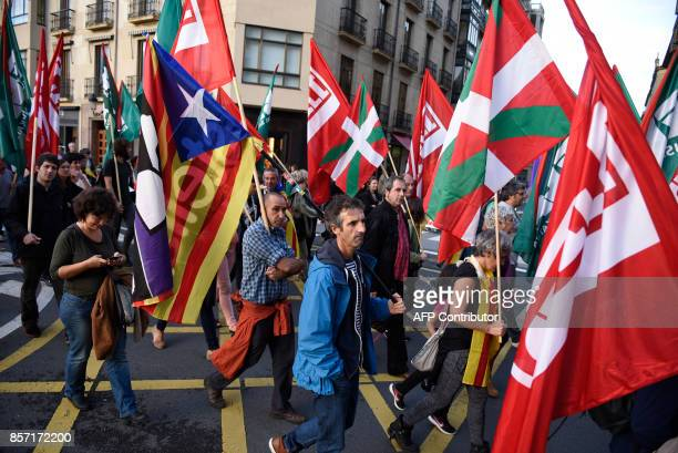 People hold Catalan proindependence 'Estelada' flags and Basque country flags during a demonstration called by Basque unions supporting the strike in...