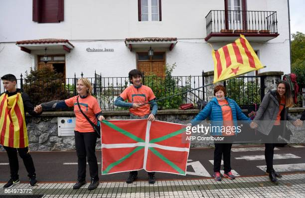 People hold Catalan proindependence Estelada flags and Basque Country flags as they take part in a human chain between villages in the northern Spain...
