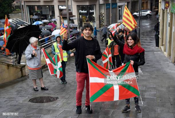 People hold Catalan proindependence Estelada flags and Basque Country flags during a demonstration in the northern Spain Basque village of Beasain on...