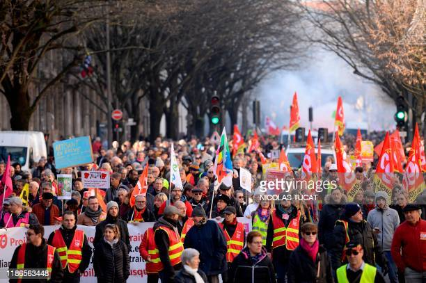 People hold CGT union flags during a demonstration against the pension overhauls in Bordeaux on December 5 as part of a national general strike...