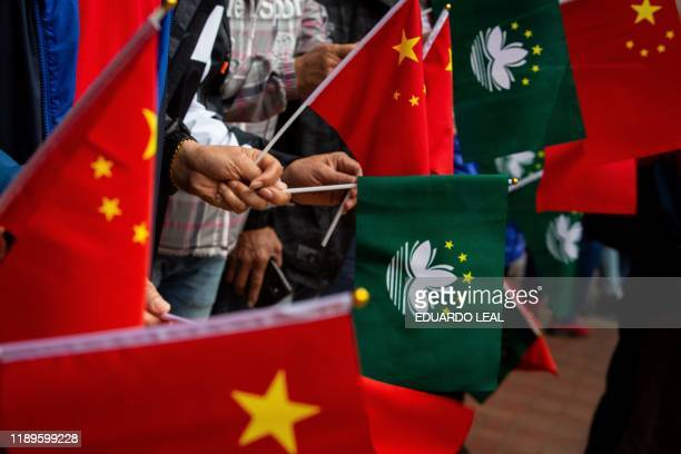People hold China and Macau flags before the motorcade of Peng Liyuan wife of China's President Xi Jinping passes after her visit to the Macau...