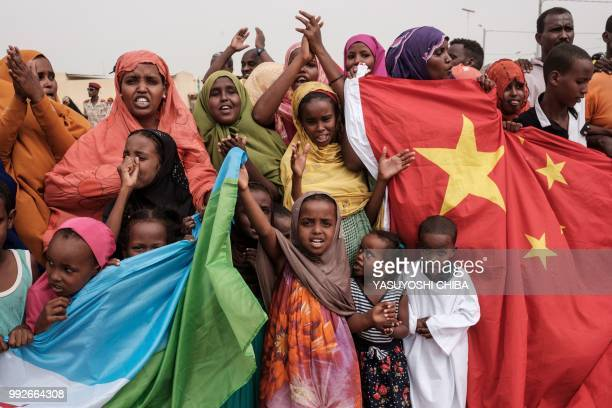 People hold Chinese and Djiboutian national flags as they wait for the arrival of Djibouti's President Ismail Omar Guellehas before the launching...