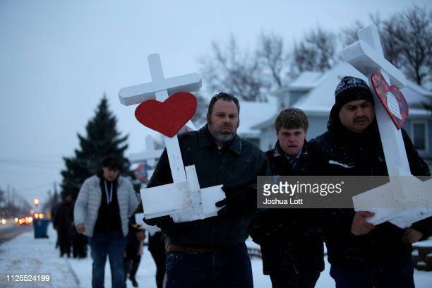 People hold crosses as they walk from Henry Pratt Company to the Aurora Police Department on February 17 2019 in Aurora Illinois Six people including...