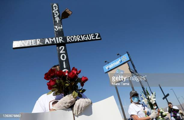 People hold crosses outside Walmart honoring those killed in the Walmart shooting which left 23 people dead in a racist attack targeting Latinos on...