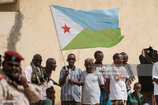 People hold Djiboutian national flag as they wait for the arrival of Djibouti's President Ismail Omar Guellehas before the launching ceremony of new...