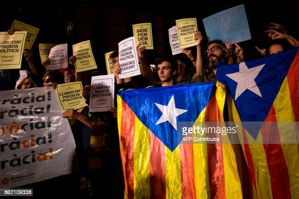 People hold Esteladas and papers reading in Catalan 'Freedom political prisoners' in front of the Generalitat Palace on October 17 2017 in Barcelona...