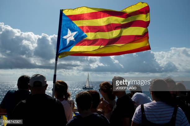 People hold Esteladas Catalan proindependence flags as they watch boats participating in a proindependence gathering under the motto Wave for the...