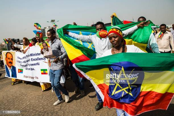 People hold Ethiopian and and Eritrean flags as they wait for the arrival of Eritrea's president and Ethiopia's prime minister at Juba International...