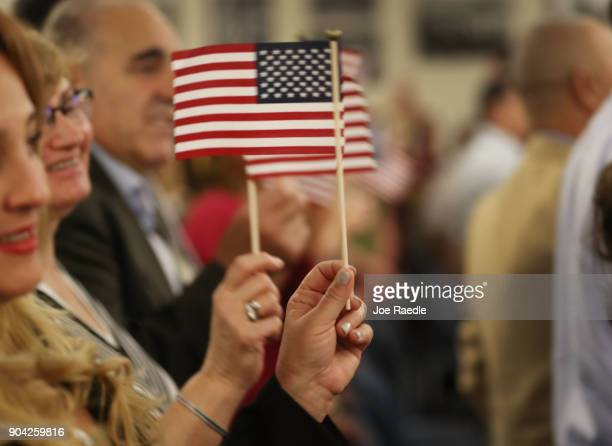 People hold flags as they are sworn in as American citizens during a US Citizenship Immigration Services naturalization ceremony at the Hialeah Field...