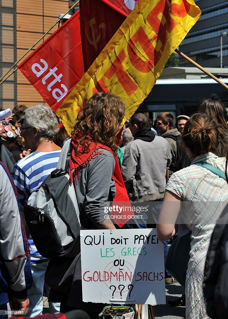 People hold flags in front of the EU Commission building on May 20,2010 in Brussels during the Brussels solidarity demonstration with working people in Greece. Actions today have been organised in Belgium in solidarity with working people in Greece. The placard reads in French 'Who should pay, Greeks or Goldman Sachs???'.