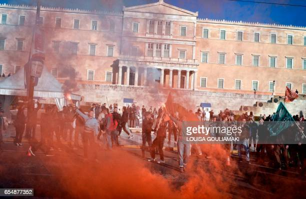 TOPSHOT People hold flares during a demonstration by Greek antifascist groups against the war in Syria and the European Union's stance on refugees on...